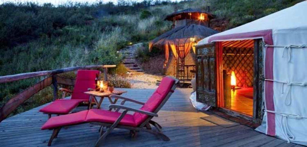 Capanne il legno per il campeggio di lusso con terrazzo esterno a doghe in legno arredato con sdraio dai cuscini fucsia e tavolino
