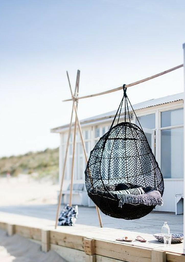 altalena a uovo appesa su sostegno in legno collocata in spiaggia