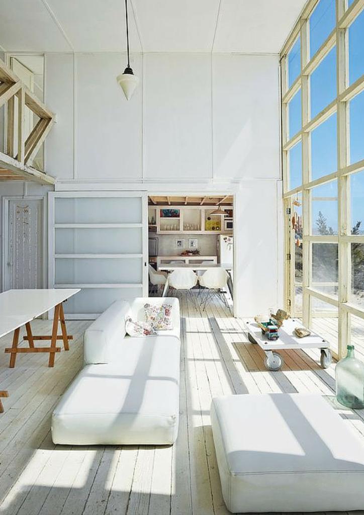 Casa al mare con interni bianchi e prospetto vetrato sulla spiaggia