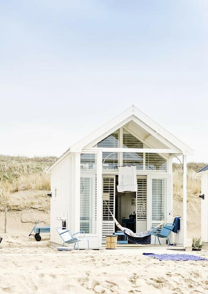 casetta con pareti in vetro e alluminio su una spiaggia
