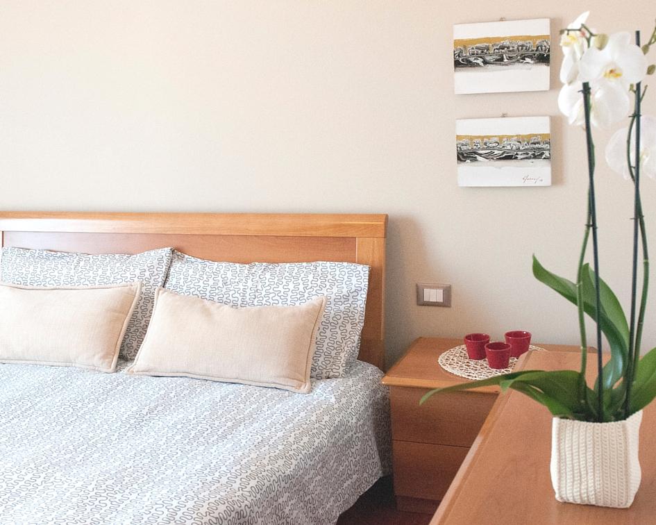 Scorcio della camera da letto in ciliegio con lenzuola bianche a motivi grafici neri e cuscini beige