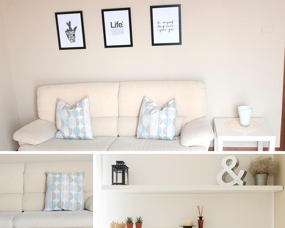 Soggiorno con divano colore crema, cuscini azzurri e crema, mobili bianchi e stampe grafiche in bianco e nero