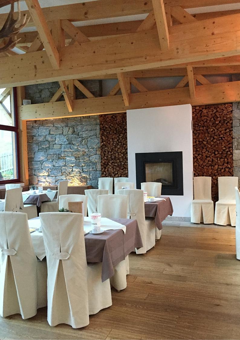 Familienhotel Bellavista Trafoi, sala da pranzo con travi in legno, parete in pietra e camino