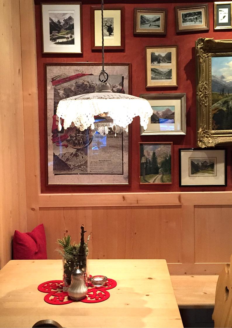 Familienhotel Bellavista Trafoi, parete rossa con boiserie in legno e fotografie
