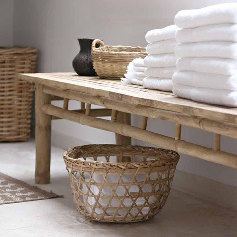 Panca da bagno in legno chiaro con appoggiati asciugamani bianchi e ...