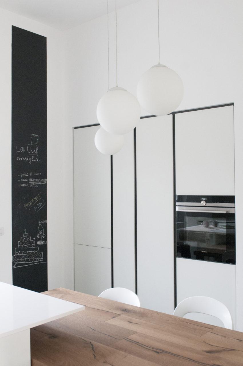 cucina in vetro bianco, gole in antracite, tavolo in legno