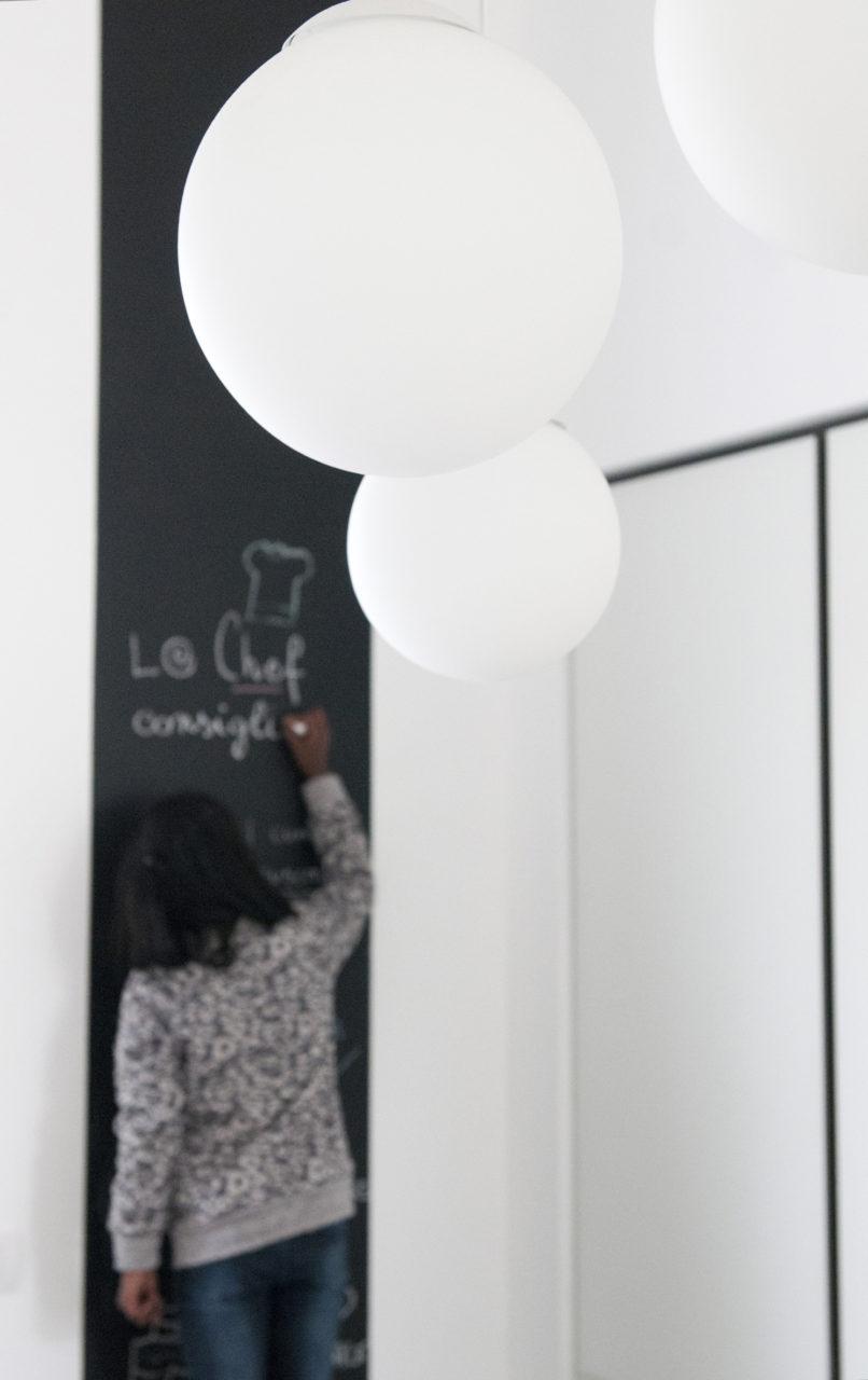 particolare angolo cucina: parete lavagna e illuminazione a sfere sospese