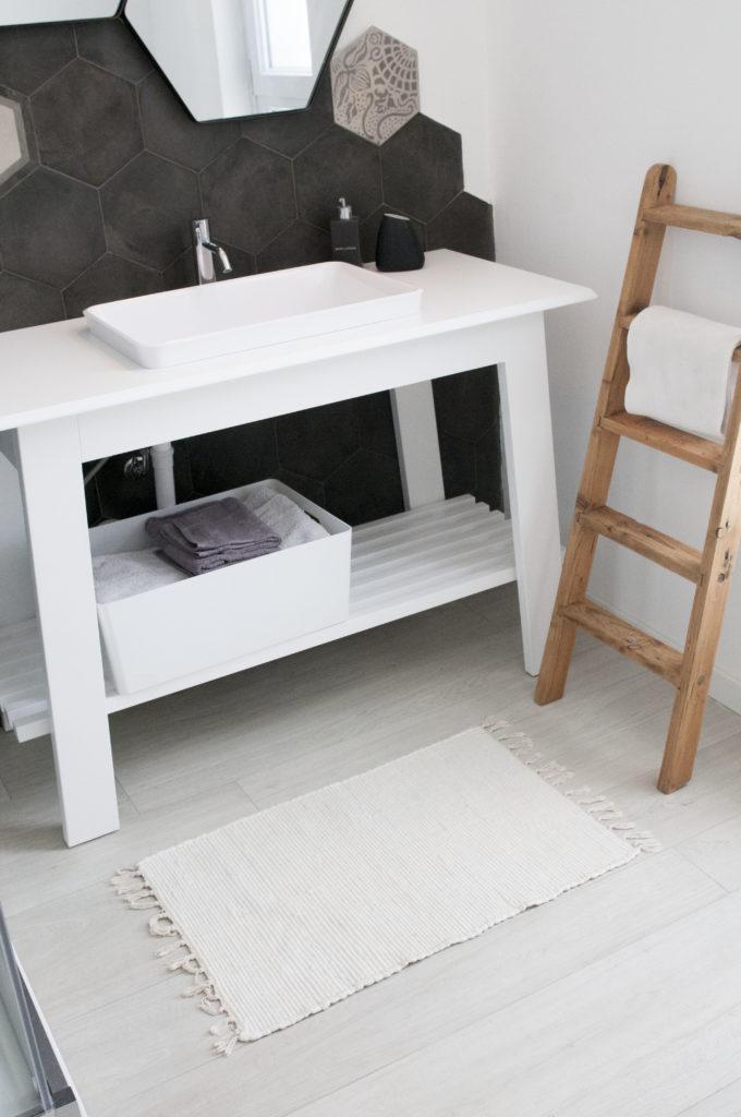 Bagno bianco e nero con mobile lavello in legno bianco