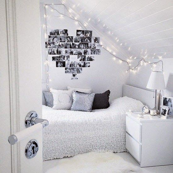 camera romantica nei toni del bianco con foto a forma di cuore appese sul muro
