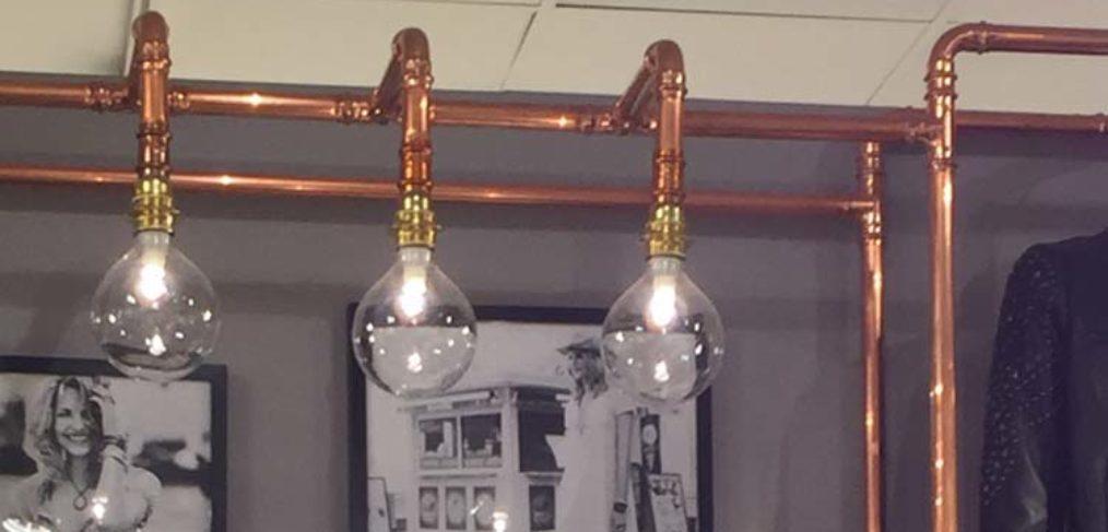 Illuminazone per negozio di abbigliamento realizzata con lampadine e tubi in rame