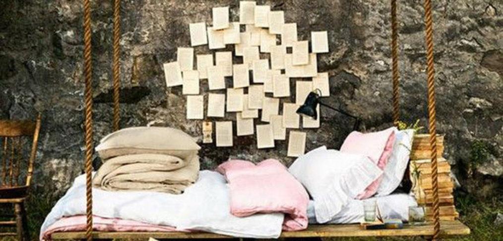 letto-altalena in legno, con coperte e cuscini, grosse corde per sostenerla e ambientazione outdoor